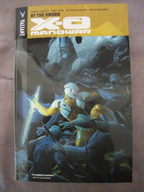 "X-O Manowar, Volume 1: By the Sword. From the Valiant Comics description: ""Aric of Dacia is a brash warrior and heir to the throne of the Visigoth people. He has lived his life under the heel of the Roman Empire, but now a far more terrible enemy has come to subjugate him. Taken from his home and family, Aric is enslaved aboard a starship belonging to a brutal race of alien colonizers known as The Vine. If he is to have any hope of escaping and returning to Earth, he will have to steal the Vine's most powerful weapon - a sentient suit of indestructible armor - and become X-O Manowar!"""